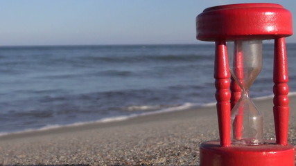 ancient red broken hourglass sandglass clock on sea beach