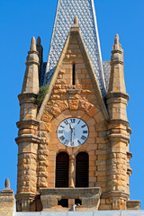 Old sandstone church tower with large clock