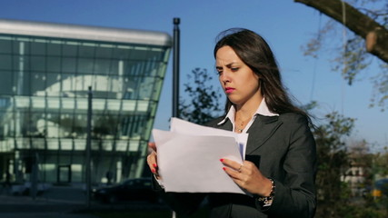 Businesswoman walking with papers and look to the camera