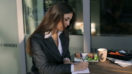 Businesswoman sitting outside the cafe and doing notes