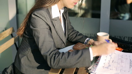 Businesswoman working on papers and smiling to the camera