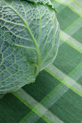 Closeup of a cabbage on a checkered tablecloth.
