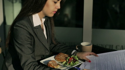 Businesswoman sitting outside the cafe and signing papers
