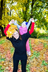 Happy mom and child girl hugging on nature at  fall