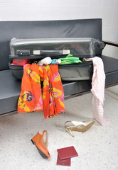 stuff and clothes travel suitcase scattered in a sofa