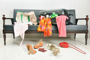 stuff and clothes suitcase scattered in a sofa