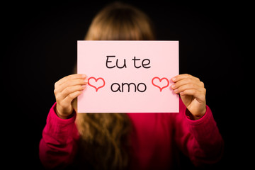 Child holding sign with Portuguese words Eu Te Amo - I Love You