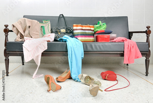 Messy clothes, lady bag and shoes scattered on a leather sofa - 73973125