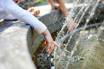 Closeup photo of child washing hands in a fountain