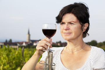 Woman with glass of red wine in vineyard