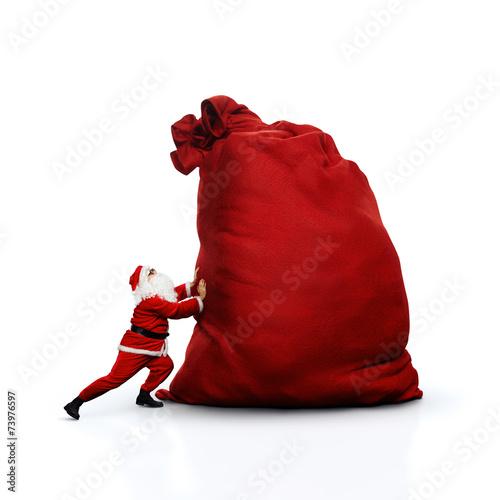 Santa pushing huge sack. Isolated on white.