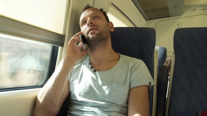 Handsome man talking on cellphone during train ride