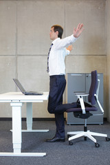 business man  stretching in standing position at desk