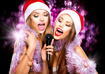 Christmas party, karaoke. Beauty girls in santa hats singing