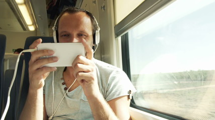 Happy man playing funny game on his smartphone during train trav