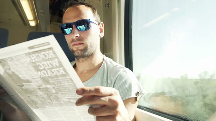 Young, handsome man reading magazine on a train