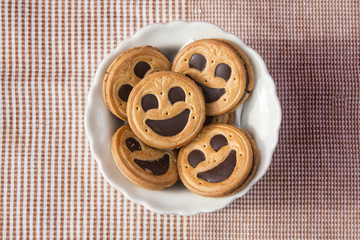 Round smiling chocolate cookies in a bowl