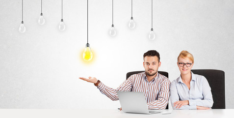 Business man and woman sitting at table with idea light bulbs