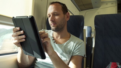 Handsome man working with tablet on a train