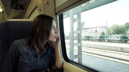 Pretty woman talking on cellphone during train ride