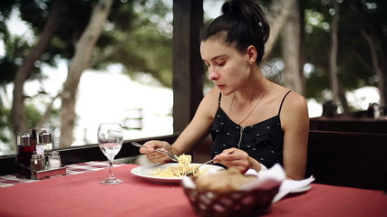 Woman eats spaghetti pasta in the restaurant on the shore