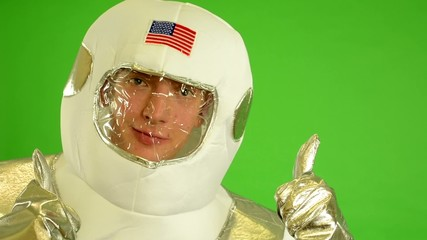 astronaut shows thumbs on agreement - green screen - closeup