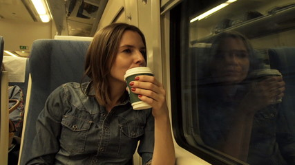 Young woman with coffee looking through the window on a train