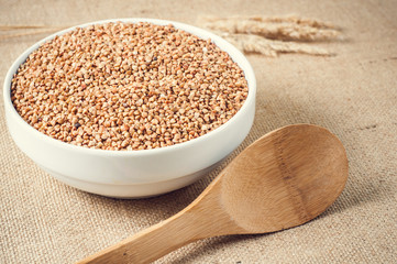 buckwheat and wooden spoon on burlap background