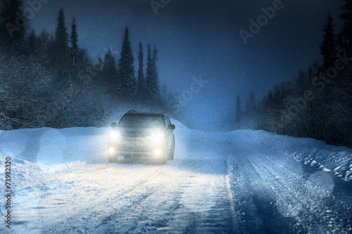 Car lights in winter forest - 73982320