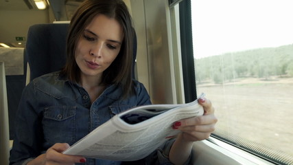 Young, attractive woman reading magazine during train travel