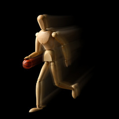 Wooden mannequin with basketball ball on black background