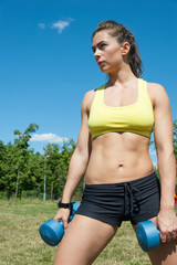 Attractive sport woman with dumbbells on playground