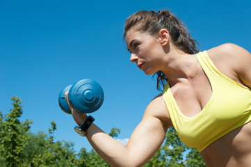 Attractive sport woman with dumbbells on the playground