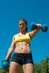 Woman with dumbbells on playground