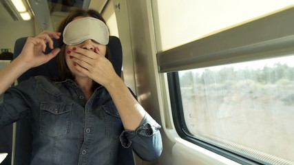 Young woman with sleeping eye mask wake up on a train