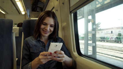 Pretty woman with smartphone sitting on a train