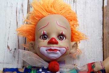 Sad old vintage doll on wooden background