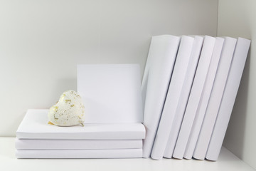 Bookshelf and books in white color, card with pace for text and