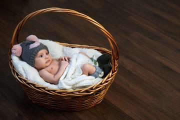 newborn baby in  cap  basket on  floor