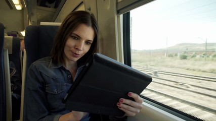 Young, pretty woman with tablet sitting on a train