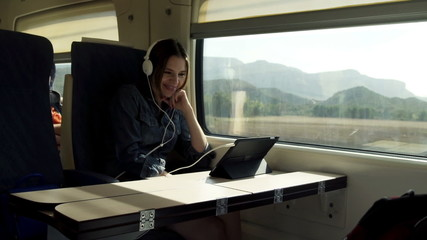 Young woman in headphones watching funny movie on tablet during