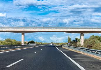 Empty asphalt road with bridge in summer.