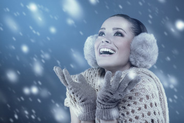 Woman in winter clothes catching snowflakes in the studio
