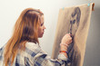 Young female artist drawing man portrait in her art studio