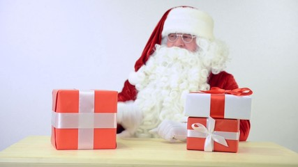 Santa Claus sitting at the table with gifts boxes.