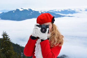 Girl with photo camera on mountain, taking pictures