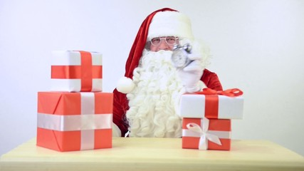 Santa Claus sitting at the table with gifts boxes and alarm