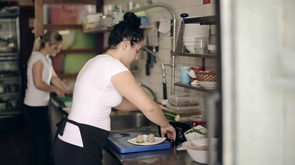 Restaurant kitchen woman preparing fish dishes for guests