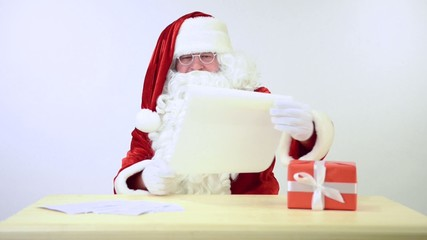 happy Santa Claus reading a letter. Isolated on white background
