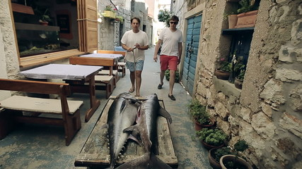 The owner of the restaurant with an assistant take fishes